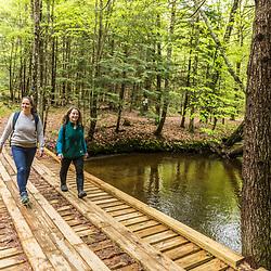 Two women walk  on a bridge crossing Mill Brook in Westbrook, Maine.