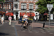 In Utrecht rijdt een meisje met de telefoon in haar hand op een damesfiets door de binnenstad.<br /> <br /> In Utrecht a girl is riding a bike in the historical center while holding her phone.