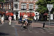 In Utrecht rijdt een meisje met de telefoon in haar hand op een damesfiets door de binnenstad.<br /> <br /> In Utrecht a girl is riding a bike in the historical center while holding her phone.