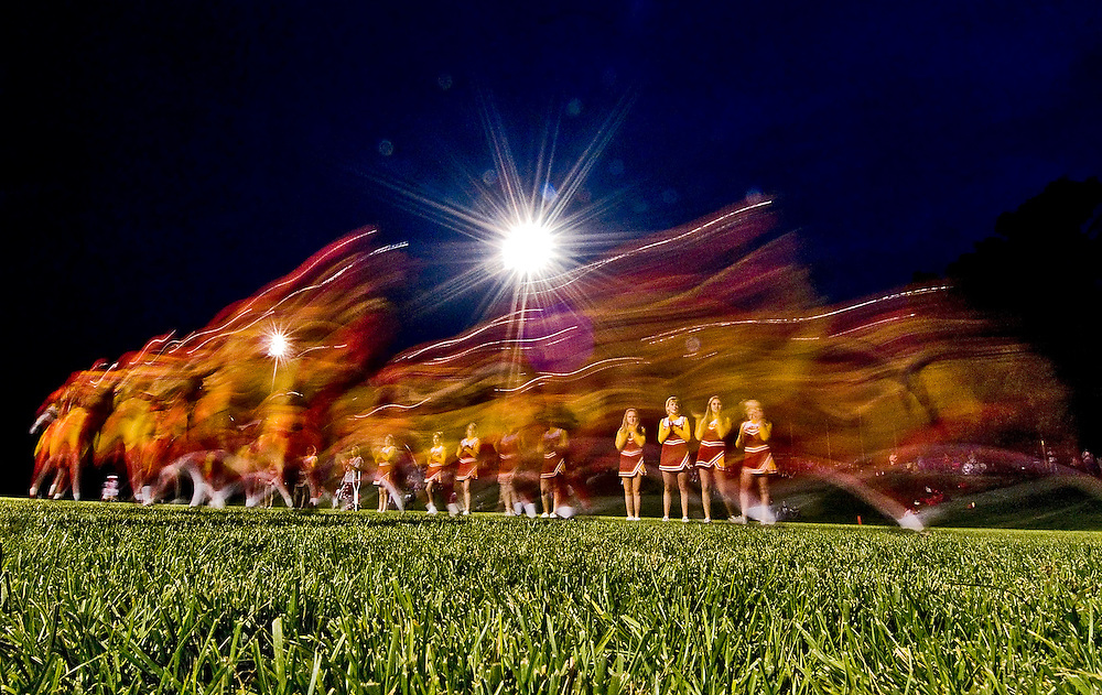 (staff photo by Matt Roth)..***This would make a great cover photo!!!***.A long camera exposure blurs members of The Golden Eagles, likening them to flames as they burst onto the the newly refurbished George Kendrick football field for the first game atop the newly sodded field, taking a big win on the field's inaugural game against the Urbana 11-13 year-old rec team, 34-14, behind Arbutus Middle School Friday night September 22, 2006. After a two-and-a-half year struggle, the field is finished and will be home to the Arbutus Big Red, the local semi-pro football team.