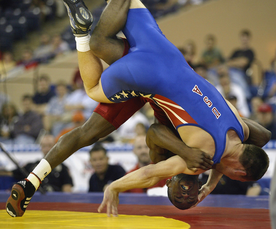 Jamill Kelly (red) flips with Jared Lawrence (blue) as he wins the third match of the of the men's 66 kg freestlye class.