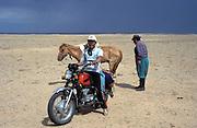 Mongolia, Gobi desert. July 1996: Munkhtsetseg's father (on right) checks one of the horses while a family friend poses on his motor bike in the Gobi desert.