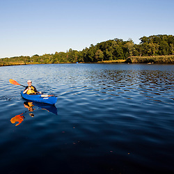 A man kayaking in the lower, tidal portion of the Taunton River in Dighton, Massachusetts.  Recently designated a Wild and Scenic River.  Summer.