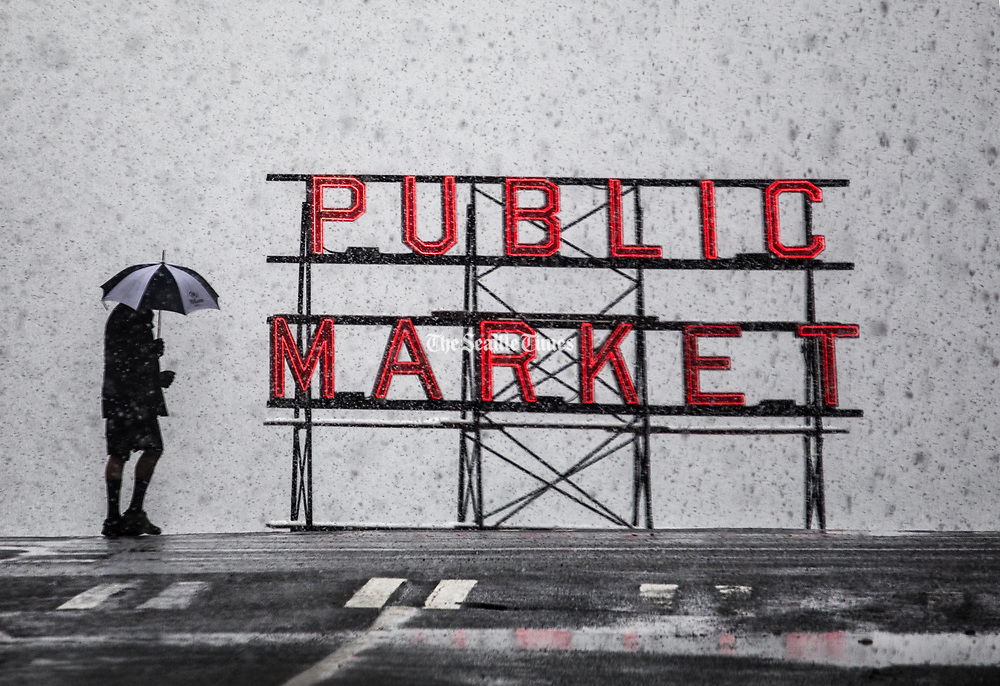 Snow falls along First Avenue in downtown Seattle, surrounding the Pike Place Market sign. (Steve Ringman / The Seattle Times)