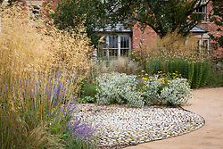 Looking towards the house with circular cobbled area and curvy path. Stipa gigantea in the foreground, Eryngium giganteum 'Miss Willmott's Ghost' beyond