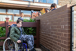 Alessandro, 12, is disabled and is unable to play in the area provided for social housing tenants, so talks to friends Gene, 11, Samuel, 13, Christine, 15 and Mason, 8. Social housing residents are up in arms after having their children forbidden from using a play area overlooked by their homes as it is said to be only available to the children of those who have bought properties at the new Baylis Old School housing development in Lambeth, South London . London, March 26 2019.