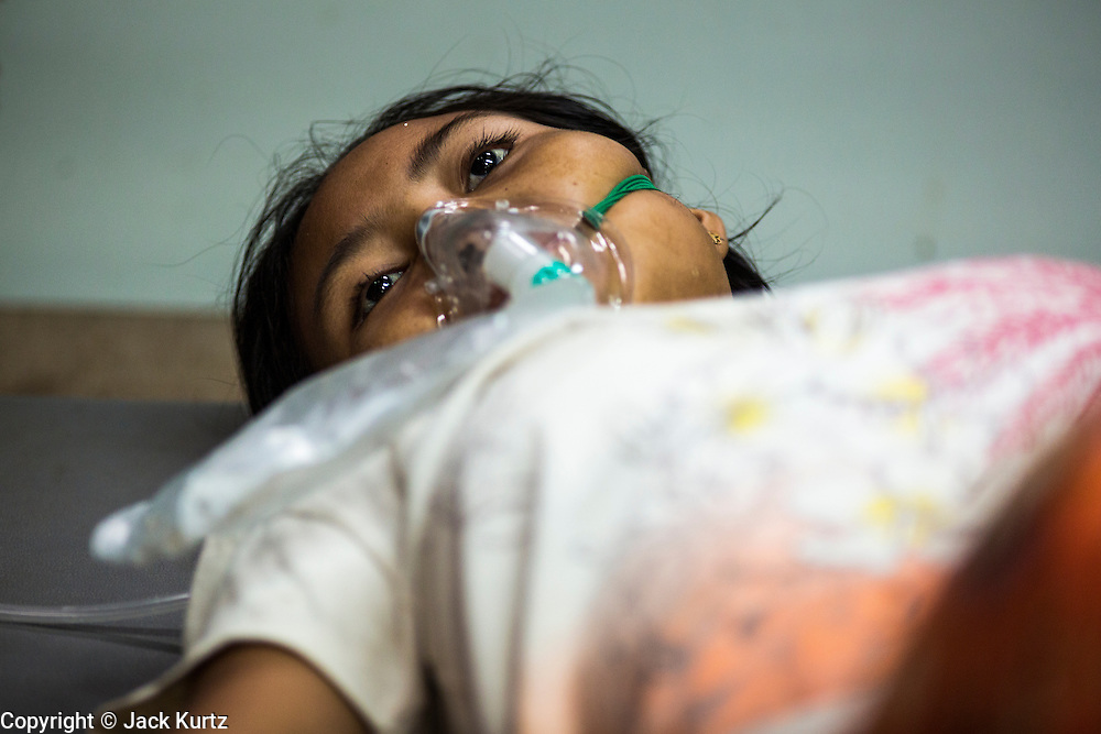 20 MAY 2013 - MAE KASA, TAK, THAILAND:  A woman who had gone into shock because of an etopic pregnancy in the SMRU clinic intensive care room at the Mae Kasa clinic. Health professionals are seeing increasing evidence of malaria resistant to artemisinin coming out of the jungles of Southeast Asia. Artemisinin has been the first choice for battling malaria in Southeast Asia for 20 years. In recent years though,  health care workers in Cambodia and Myanmar (Burma) are seeing signs that the malaria parasite is becoming resistant to artemisinin. Scientists who study malaria are concerned that history could repeat itself because chloroquine, an effective malaria treatment until the 1990s, first lost its effectiveness in Cambodia and Burma before spreading to Africa, which led to a spike in deaths there. Doctors at the Shaklo Malaria Research Unit (SMRU), which studies malaria along the Thai Burma border, are worried that artemisinin resistance is growing at a rapid pace. Dr. Aung Pyae Phyo, a Burmese physician at a SMRU clinic just a few meters from the Burmese border, said that in 2009, 90 percent of patients were cured with artemisinin, but in 2010, it dropped to about 70 percent and is now between 55 and 60 percent. He said the concern is that as it becomes more difficult to clear the parasite from a patient, progress that has been made in combating malaria will be lost and the disease could make a comeback in Southeast Asia.    PHOTO BY JACK KURTZ