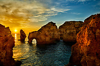 Sun rises over the ocean and among the rock formations along the coast in the town of Lagos in the Algarve region of southern Portugal.