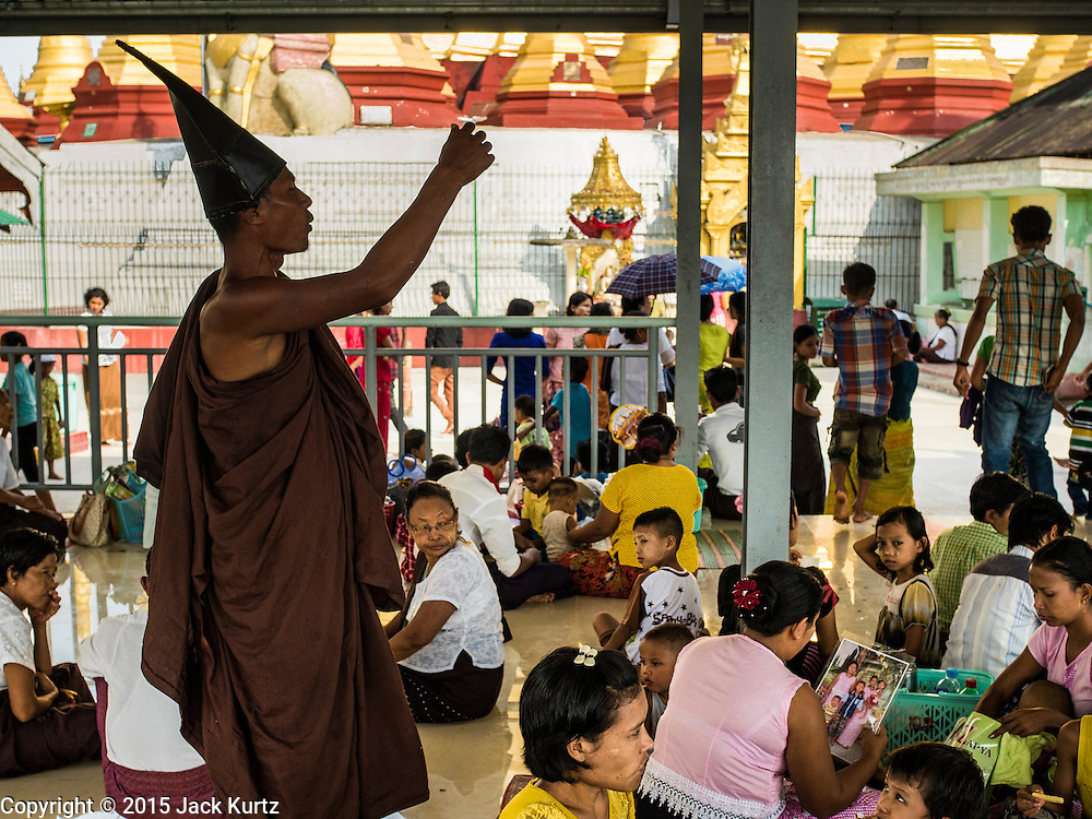 """28 OCTOBER 2015 - THANLYNN, MYANMAR:  A """"Hermit Monk"""" talks to Buddhists in a prayer hall at Kyaik Khauk Pagoda during observances of Thadingyut. The Thadingyut Festival, the Lighting Festival of Myanmar, is held on the full moon day of the Burmese Lunar month of Thadingyut. As a custom, it is held at the end of the Buddhist lent (Vassa). The Thadingyut festival is the celebration to welcome the Buddha's descent from heaven.     PHOTO BY JACK KURTZ"""