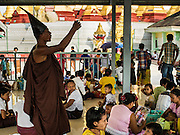 "28 OCTOBER 2015 - THANLYNN, MYANMAR:  A ""Hermit Monk"" talks to Buddhists in a prayer hall at Kyaik Khauk Pagoda during observances of Thadingyut. The Thadingyut Festival, the Lighting Festival of Myanmar, is held on the full moon day of the Burmese Lunar month of Thadingyut. As a custom, it is held at the end of the Buddhist lent (Vassa). The Thadingyut festival is the celebration to welcome the Buddha's descent from heaven.     PHOTO BY JACK KURTZ"