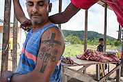 The tattoo on the butcher's arm is clearly showing how catholicism is well rooted in the Amerindian Communities (Annai, North Rupununi)