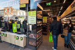 "© Licensed to London News Pictures. 07/03/2021. LONDON, UK.  Customers shop inside the new 2,500 sq ft Amazon Fresh store in Ealing, west London on its first weekend of opening. It is the first ""just walk out"" grocery store in the UK and the first outside the USA.  As a ""contactless"" shop, it is available to anyone signed up to Amazon and with the app on their smartphone.  In-store cameras and artificial intelligence monitor customers picking up items who simply walk out and billing takes place later automatically.  Photo credit: Stephen Chung/LNP"