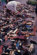 An French elderly lady bends down to find the right shoes for herself among dozens of other pairs in all styles and sizes strewn on the ground in the weekly market, on 11th May 1990, in Calais, France.