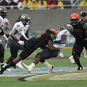Quarterback Quentin WIlliams (3) gets tackled by Florida A&M Rattlers cornerback Devonte Johnson (4) during the Florida Classic NCAA football game between the FAMU Rattlers and the Bethune Cookman Wildcats at the Florida Citrus bowl on Saturday, November 22, 2014 in Orlando, Florida. (AP Photo/Alex Menendez)