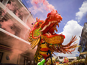 """05 JULY 2014 - BANGKOK, THAILAND: A dragon breathing fire (from fireworks placed inside its head) on a side street in Bangkok during a parade for vassa. Vassa, called """"phansa"""" in Thai, marks the beginning of the three months long Buddhist rains retreat when monks and novices stay in the temple for periods of intense meditation. Vassa officially starts July 11 but temples across Bangkok are holding events to mark the holiday all week.    PHOTO BY JACK KURTZ"""