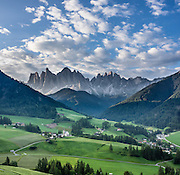 Views of the Geisler/Odle Group and a church in St. Magdalena (Santa Maddalena) village are iconic of the Dolomites mountains. See the valley and municipality of Funes (Villnöss) in Trentino-Alto Adige/Südtirol (South Tyrol), Italy. Enjoy great hiking here in the vast Nature Park of Parco Naturale Puez-Odle (German: Naturpark Puez-Geisler; Ladin: Parch Natural Pöz-Odles). The Dolomites are part of the Southern Limestone Alps, Europe. UNESCO honored the Dolomites as a natural World Heritage Site in 2009. This panorama was stitched from 2 overlapping photos.