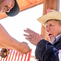 Stan Bobcat, left, serves fresh roasted mutton Ned Chee during a traditional butchering event at Red Rock Care Center in Gallup Friday.