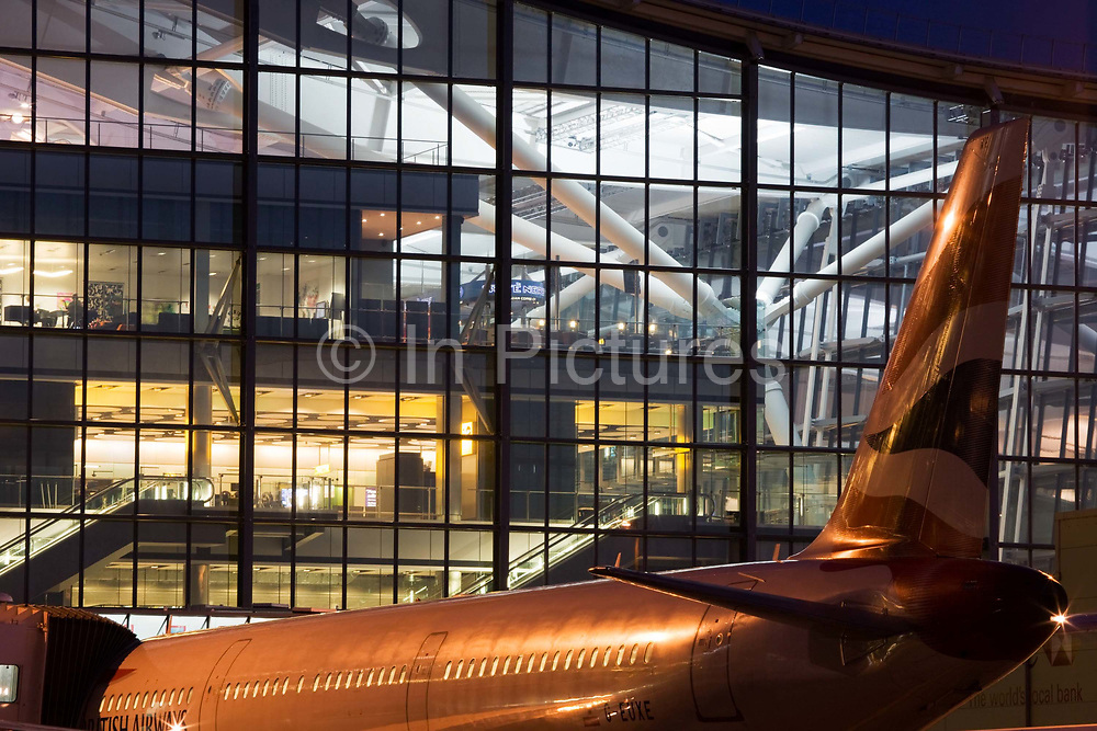 """An exterior view of Heathrow Airport's Terminal 5 building in West London. Created by the Richard Rogers Partnership (now Rogers Stirk Harbour and Partners). A British Airways airliner is parked at its Arrival/Departure gate in front of the bright lights that shine through huge window panes of glass. At a cost of £4.3 billion, the 400m long T5 is the largest free-standing building in the UK with the capacity to serve around 30 million passengers a year. The Terminal 5 public inquiry was the longest in UK history, lasting four years from 1995 to 1999. From writer Alain de Botton's book project """"A Week at the Airport: A Heathrow Diary"""" (2009)."""