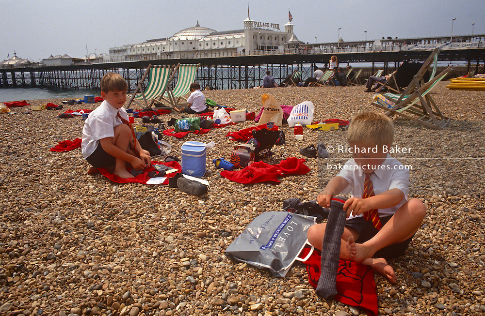 Schoolboys get dressed after an afternoon off from classes, spent next to the western Palace Pier at the seaside town of Brighton. Pulling on socks is a young lad from a nearby school whose uniform is a red blazer and striped tie. With their clothing of their friends still lie on the shngle, their afternoon of play day is coming to an end. In the background is the western Palace Pier, a major landmark on this south coast resort. Ofsted's guidelines are that for children of 9-12, a ratio of one adult to 8 young people is a requirement.