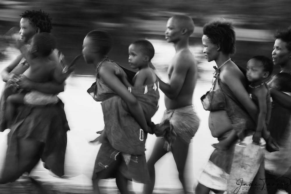 A black and white motion-blur of  San bushmen women and children walking, Kalahari, Botswana, Africa