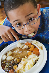 Boy with Cerebral Palsy eating his school dinner,