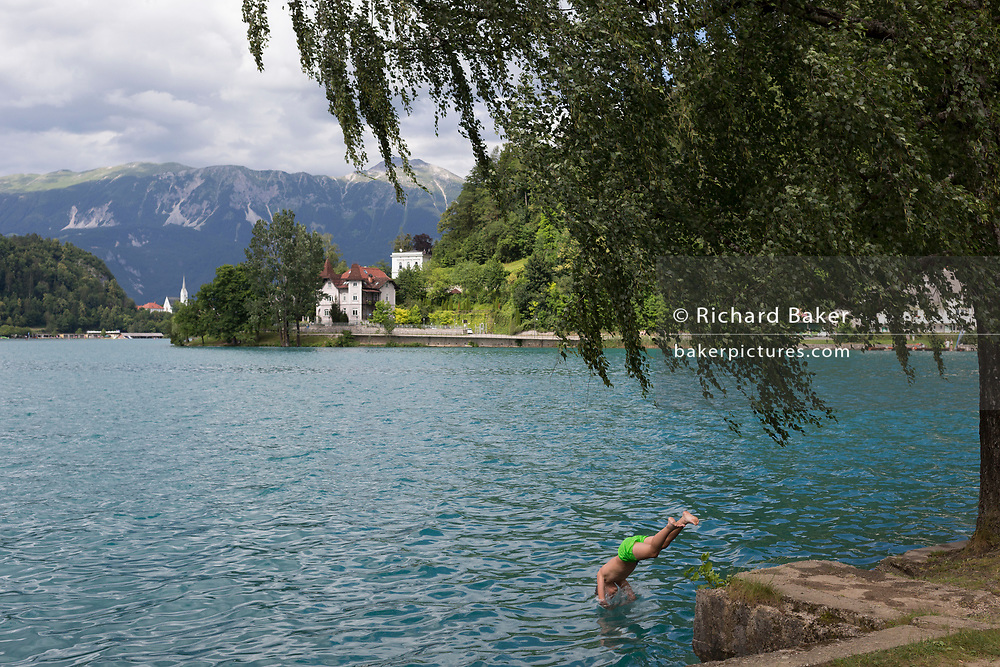 A boy dives into the cool waters of Lake Bled, on 18th June 2018, in Bled, Slovenia.