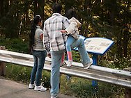 An Asian family read an information sign that tells about Alder Dam on the Nisqually River which generates power for Tacoma City Light, Washington, USA
