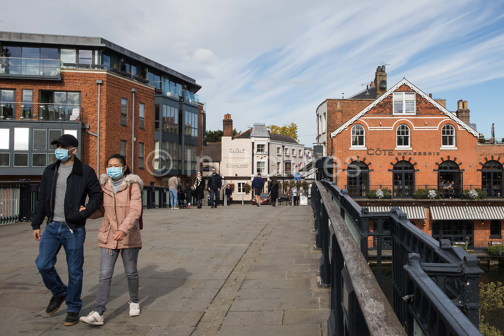 Visitors wearing face coverings to help prevent the spread of the coronavirus cross Eton Bridge on 26 September 2020 in Windsor, United Kingdom. The Royal Borough of Windsor and Maidenhead is aware of a rise in local coronavirus infections, has a COVID-19 outbreak management plan in place to try to ensure that the numbers do not increase further and has requested access to more coronavirus testing sites with this in mind.