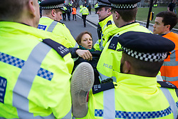 London, UK. 17th April 2019. Police officers arrest a climate change activist from Extinction Rebellion in Parliament Square as part of an operation to try to clear protesters taking part in the International Rebellion in order to reopen the square to traffic.