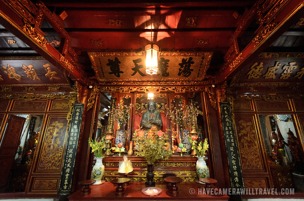 The ornate interior of one of the outer shrines at Quan Thanh Temple in Hanoi. The statue, measuring nearly 4 meters tall and weighing nearly 4 tons was cast in 1677 and depicts Huyen Thien Tran Vo, the God who administered the North and after whom the temple was originally named. The Taoist temple dates back to the 11th century and is located close to West Lake (Ho Tay).