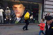 A police officer carries a yellow bag that resembles the old-fashioned idea of swag (stolen goods) but may be evidence from a nearby crime. Alongside is a large image of a male model in the window of clothing retailer H&M on Regents Street, London borough of Westminster. In 1947 Hennes women's clothing store opened in Västerås, Sweden. Today the H&M Group offers fashion for everyone under the brands of H&M, COS, Monki, Weekday, Cheap Monday and & Other Stories, as well as fashion for the home at H&M Home.