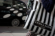 In a scene about consumerism, a shopper carrying a striped shopping bag for the brand India Jane, walks past a car featuring spots, on 23rd September 2016, in New Bond Street, central London, England. India Jane is a label of furniture and collections of home interiors accessories.