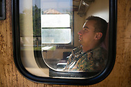 A soldier in the Bosnian army sitting alone in a train compartment, traveling in the early morning from Mostar to Sarajevo