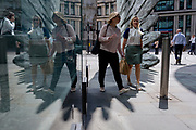 Financial industry businesswomen walk past the sculpture entitled City Wing on Threadneedle Street in the City of London, the capital's financial district (aka the Square Mile), on 11th July 2019, in London, England. City Wing is by the artist Christopher Le Brun. The ten-metre-tall bronze sculpture is by President of the Royal Academy of Arts, Christopher Le Brun, commissioned by Hammerson in 2009. It is called 'The City Wing' and has been cast by Morris Singer Art Founders, reputedly the oldest fine art foundry in the world.