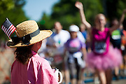 A woman wearing an American flag and straw hat watches the 2012 Bolder Boulder 10K road race in Boulder, Colorado.