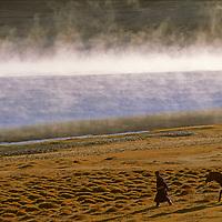 MONGOLIA. Horseman walks beside morning mist on (Lake) Dood Nuur, Darhad Valley