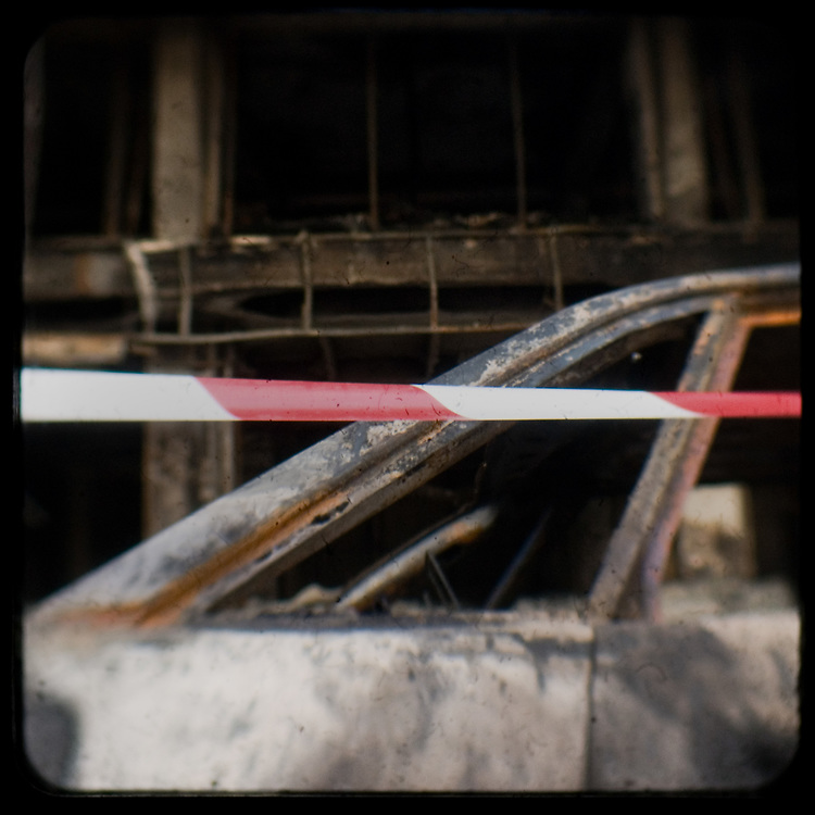 A burned out car and building on Ermou Street. <br /> <br /> Following the murder of a 15 year old boy, Alexandros Grigoropoulos, by a policeman on 6 December 2008 widespread riots, protests and unrest followed lasting for several weeks and spreading beyond the capital and even overseas<br /> <br /> When I walked in the streets of my town the day after the riots I instantly forgot the image I had about Athens, that of a bustling, peaceful, energetic metropolis and in my mind came the old photographs from WWII, the civil war and the students uprising against the dictatorship. <br /> <br /> Thus I decided not to turn my digital camera straight to the destroyed buildings but to photograph through an old camera that worked as a filter, a barrier between me and the city.
