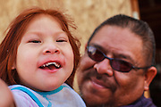 "12 JULY 2012 - FT DEFIANCE, AZ:  ART MOORE and his granddaughter, LORELLE MIKE, 2 years old, wait for the revival to start at the 23rd annual Navajo Nation Camp Meeting in Ft. Defiance, north of Window Rock, AZ, on the Navajo reservation. Preachers from across the Navajo Nation, and the western US, come to Navajo Nation Camp Meeting to preach an evangelical form of Christianity. Evangelical Christians make up a growing part of the reservation - there are now more than a hundred camp meetings and tent revivals on the reservation every year. The camp meeting in Ft. Defiance draws nearly 200 people each night of its six day run. Many of the attendees convert to evangelical Christianity from traditional Navajo beliefs, Catholicism or Mormonism. ""Camp meetings"" are a form of Protestant Christian religious services originating in Britain and once common in rural parts of the United States. People would travel a great distance to a particular site to camp out, listen to itinerant preachers, and pray. This suited the rural life, before cars and highways were common, because rural areas often lacked traditional churches.  PHOTO BY JACK KURTZ"