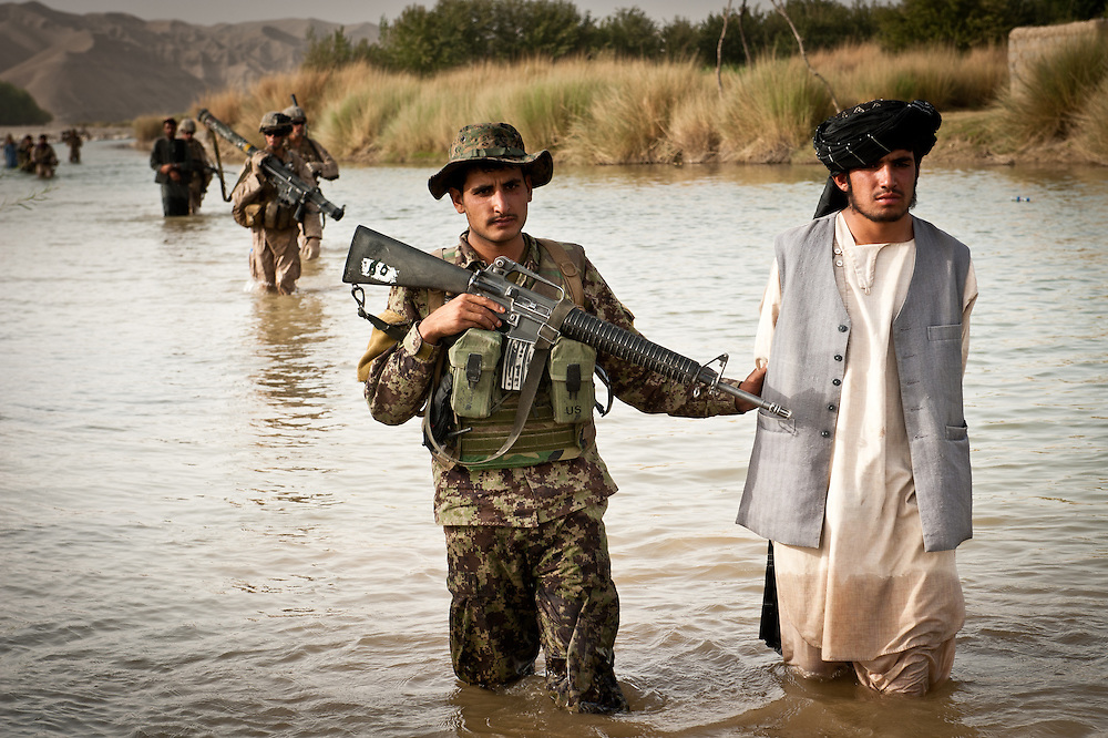 An Afghan National Army soldier leads a detained Afghan insurgent back to PB Fires through the Helmand River.