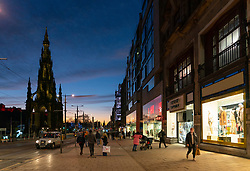 Edinburgh, Scotland, UK. 24 December 2020. Beautiful Christmas Eve and Brexit Deal sunset over Edinburgh viewed along a quiet Princes Street with a few shoppers making last minute Christmas present purchases in the sales. .Iain Masterton/Alamy Live News.