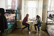 Syrian Christians Razan Karoni (left) with her friend Bernadette, 13, in their shared bedroom opposite the Samatya Kilisesi (church) in Istanbul, Turkey. Razan is waiting in Istanbul before being resettled to Australia