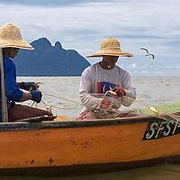 Two fishermen hauling their net.
