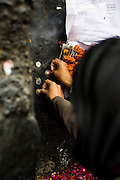 """18th December 2014, New Delhi, India. Women press coins onto a wall as  offerings and ask for wishes to be granted by Djinns in the ruins of Feroz Shah Kotla in New Delhi, India on the 18th December 2014<br /> <br /> PHOTOGRAPH BY AND COPYRIGHT OF SIMON DE TREY-WHITE a photographer in delhi<br /> + 91 98103 99809. Email: simon@simondetreywhite.com<br /> <br /> People have been coming to Firoz Shah Kotla to leave written notes and offerings for Djinns in the hopes of getting wishes granted since the late 1970's. Jinn, jann or djinn are supernatural creatures in Islamic mythology as well as pre-Islamic Arabian mythology. They are mentioned frequently in the Quran  and other Islamic texts and inhabit an unseen world called Djinnestan. In Islamic theology jinn are said to be creatures with free will, made from smokeless fire by Allah as humans were made of clay, among other things. According to the Quran, jinn have free will, and Iblis abused this freedom in front of Allah by refusing to bow to Adam when Allah ordered angels and jinn to do so. For disobeying Allah, Iblis was expelled from Paradise and called """"Shaytan"""" (Satan).They are usually invisible to humans, but humans do appear clearly to jinn, as they can possess them. Like humans, jinn will also be judged on the Day of Judgment and will be sent to Paradise or Hell according to their deeds. Feroz Shah Tughlaq (r. 1351–88), the Sultan of Delhi, established the fortified city of Ferozabad in 1354, as the new capital of the Delhi Sultanate, and included in it the site of the present Feroz Shah Kotla. Kotla literally means fortress or citadel."""