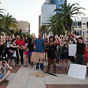 """People raise their arms in unison at Lake Eola park during the """"National Moment of Silence"""" event at the Lake Eola bandshell in downtown Orlando, Florida on Thursday, August 14, 2014. In light of the recent killing of eighteen year old Mike Brown in Ferguson, Missouri, citizens across America are gathering in solidarity to hold vigils and observe a moment of silence to honor victims of suspected police brutality. (AP Photo/Alex Menendez)"""
