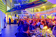 Garden City, NY, U.S., Nov. 14, 2019. HUNTLEY LAWRENCE, the Aviation Leadership Award honoree, speaks at podium in distance under U.S. Navy Grumman F11 jet suspended from atrium ceiling, as guests look on during 7th Annual Cradle of Aviation Museum Air & Space Gala.