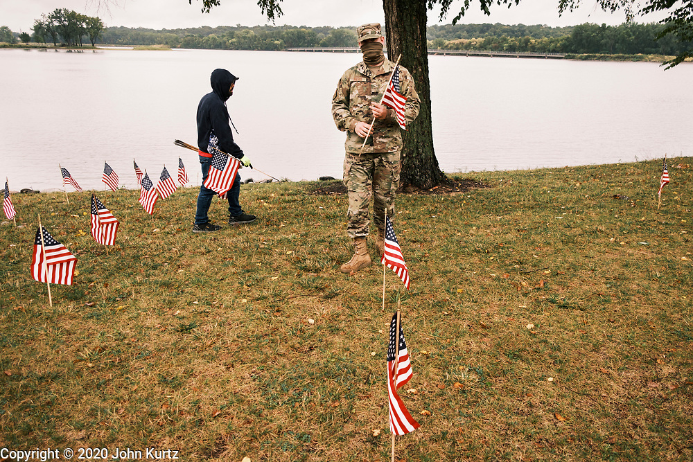 10 SEPTEMBER 2020 - DES MOINES, IOWA: A US Air Force Airman and a volunteer set out American flags in Des Moines. About 25 volunteers braved cold and rainy weather Thursday to line the west end of Gray's Lake in Des Moines with American flags. The display of the flags was a part of an annual event called the 9/11 Tribute Trail. About 3,000 flags were set out in memorial of the 3,000 people killed in the 9/11 terrorist attacks.     PHOTO BY JACK KURTZ