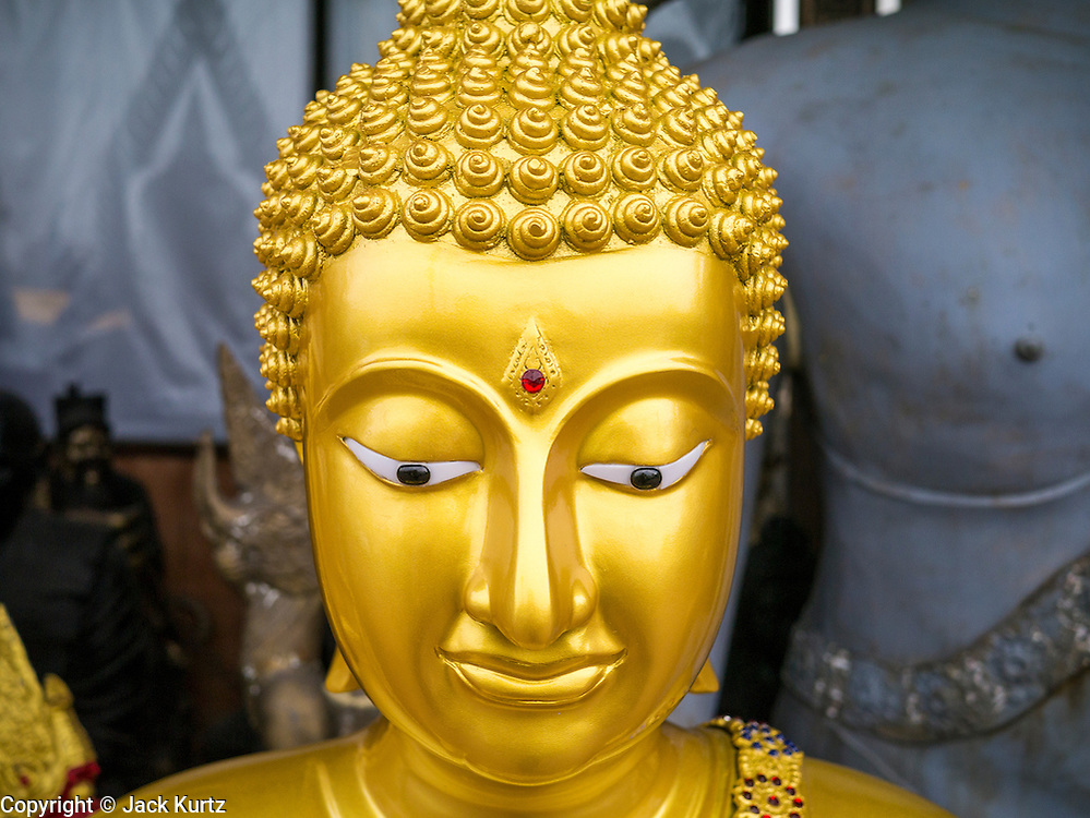 """12 NOVEMBER 2012 - BANGKOK, THAILAND:   A Buddha statue for sale on Bamrung Muang Street in Bangkok. Thanon Bamrung Muang (Thanon is Thai for Road or Street) is Bangkok's """"Street of Many Buddhas."""" Like many ancient cities, Bangkok was once a city of artisan's neighborhoods and Bamrung Muang Road, near Bangkok's present day city hall, was once the street where all the country's Buddha statues were made. Now they made in factories on the edge of Bangkok, but Bamrung Muang Road is still where the statues are sold. Once an elephant trail, it was one of the first streets paved in Bangkok. It is the largest center of Buddhist supplies in Thailand. Not just statues but also monk's robes, candles, alms bowls, and pre-configured alms baskets are for sale along both sides of the street.    PHOTO BY JACK KURTZ"""