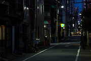 A Japanese male office worker, or salaryman, walks down a small street in Ueno at night. Tokyo, Japan. Monday April 15th 2019
