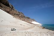 Car driving along dunes at the foot of cliffs at Arhur, Socotra, Yemen
