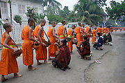 """15 MARCH 2009 -- LUANG PRABANG, LAOS: Buddhist Monks in Luang Prabang, Laos, go about their """"Tak Bat,"""" Lao for """"monks morning rounds."""" The monks collect alms in the form of food from people who line their route. For the monks, it is the only food they get that day, for the people it's a chance to """"make merit."""" Luang Prabang is a UNESCO World Heritage Site and the spiritual capital of Laos. There are dozens of """"wats"""" or temples and thousands of monks in the city. It is still the center of Buddhist education in Laos. PHOTO BY JACK KURTZ"""